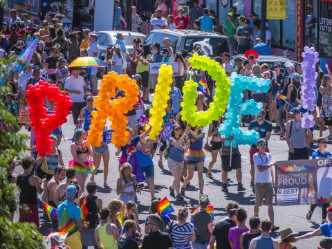 Revelers carry colorful balloons during the Denver Pridefest parada
